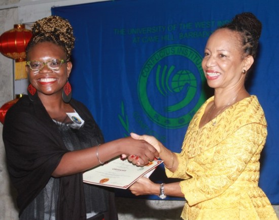 Anya Lewis, winner of the Chinese Bridge –– Chinese Proficiency Competition, receiving her award from UWI Cave  Hill principal Eudine Barriteau  (at right).