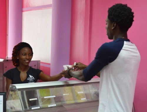 A customer receiving his ice cream from cashier Cherene Ward.