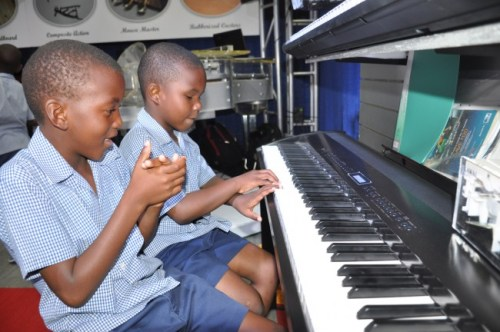 A focused Nathan Small (right) of Belmont Primary School  playing a tune on the piano at the Pianoman Caribbean booth  as his classmate Kemar Johnson sits supporting him.