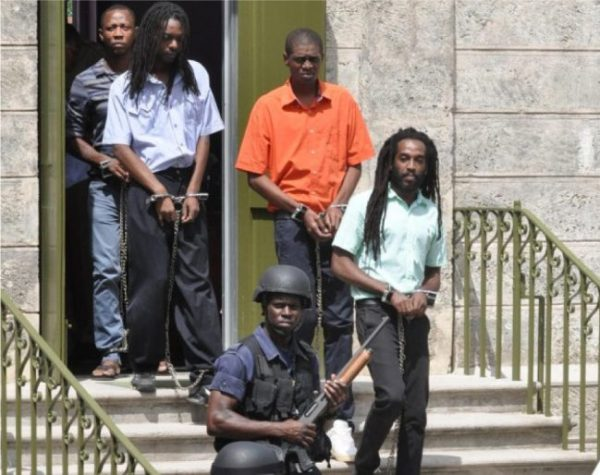 """Andre """"Lord Evil"""" Jackman (green shirt) and some of the co-accused in the murder of Charley Dume leaving court last year."""
