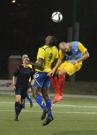 Barbadian striker Mario Harte clears the ball away from Francois Croes of Aruba.
