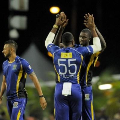 Barbados Tridents' Jason Holder (facing) is congratulated by his captain Kieron Pollard.