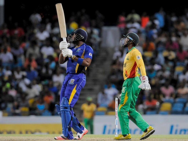 Barbados Tridents' captain Kieron  Pollard hits a six as Warriors' captain Denesh Ramdin watches.