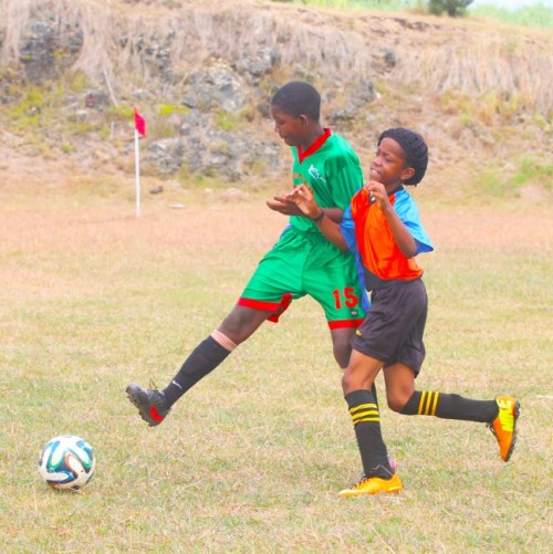 Hillaby Turners Hall defender Tidre Arthur (left) cleared the ball away from Nyerer Maughan of Wilkie Cumberbatch.