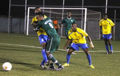 Jason King of Wales (in green) tries to fight his way through Notre Dame's strong defence made up goal-scorer Giancarlo Cobham (left) and Renaldo Gilkes.