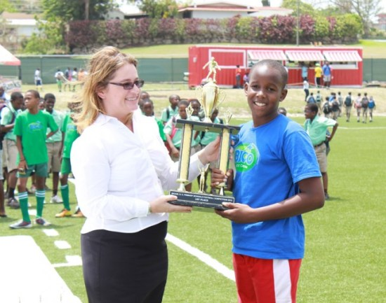 St Stephen's Primary's captain Kyrone Alexander receiving the winners' trophy from BICO general manager Joanne Pooler.