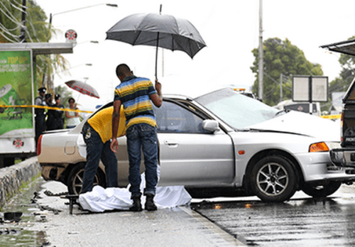 Undertakers remove the bodies of Dave Christian and Isiah Jones, both of Block 22, Laventille, who were killed when the car in which they were travelling crashed into another on the Priority Bus Route near Sixth Avenue, Barataria, yesterday morning.