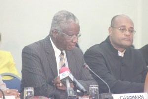 Prime Minister Freundel Stuart (left) making a point at today's meeting of the Social Partnership as Minister of State Patrick Todd looked on.