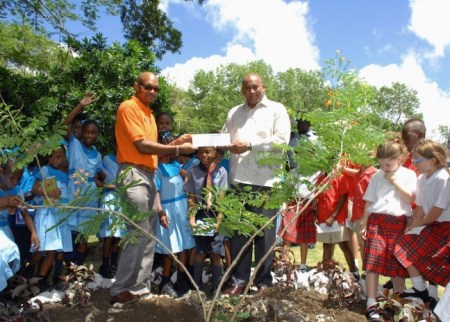 Paul Collymore, operations manager of Ocean Two Resort, presenting Acting Prime Minister Richard Sealy with a cheque.
