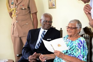 Governor General Sir Elliott Belgrave (left) looking on with delight as centenarian Helen Lizetta Hutchinson admires her birthday card.