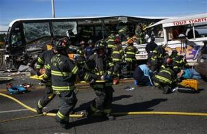 """Emergency personnel working at the scene of a fatal collision involving a charter bus, background, and a """"Ride The Ducks"""" amphibious tour bus, right, on the Aurora Bridge in Seattle today."""