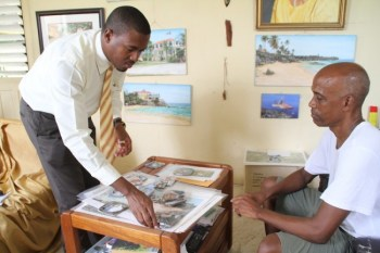 Artist Victor Collector (right) looking on as Barbados TODAY reporter Marlon Madden examines some of his work.