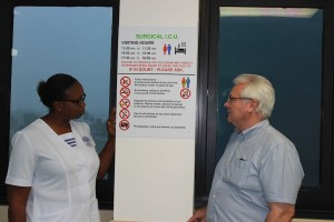Trustee of the John Thompson Memorial Trust Fund Ronald Jones (right) and nursing officer Lisa Assgill viewing the new sign, designed by Jones, highlighting the rules of the Unit .