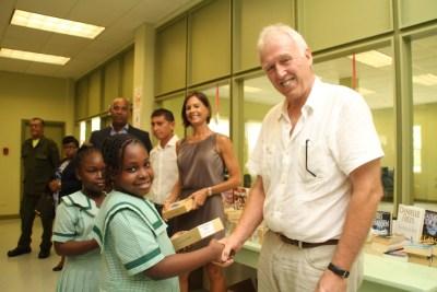 Visitor Nic Williamson (right) making presentation to  Lathoria Belgrave  of St Bernard Primary School.