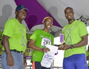 Marlo Hunte accepts here prizes from Sagicor executives Anderson King (right) and Roger Spencer.
