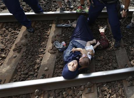 A migrant lying on the track with a baby as she was detained in Bicske, Hungary. Over 150,000 migrants have reached Hungary this year, most coming through the southern border with Serbia. Many apply for asylum but quickly try to leave for richer EU countries.