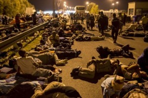 Migrants sleeping on a highway in front of a barrier at the border with Hungary near the village of Horgos, Serbia, today.