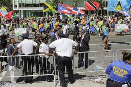 New York City Police officers studying the scene of a fatal stabbing in the Brooklyn borough of New York as participants in the West Indian Day Parade pass behind them.