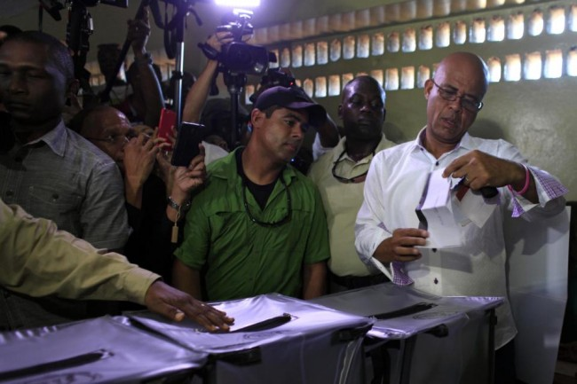 Haiti's President Michel Martelly double checks his ballot before casting it during elections in the Petion-Ville suburb of Port-au-Prince, Haiti, Sunday, Oct. 25, 2015. The country is holding the first-round presidential vote Sunday along with balloting for numerous legislative races and local offices. (AP Photo/Ricardo Arduengo)