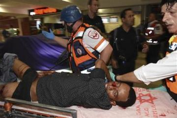 Mulu Habtom Zerhoma,  a wounded Eritrean, being evacuated from the scene of an attack in Beersheba, Israel.