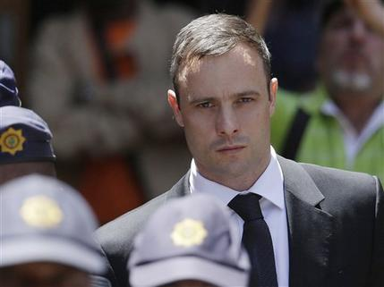 In this October 17, 2014 file photo, Oscar Pistorius is escorted by police officers  as he leaves the high court in Pretoria,  South Africa. Pistorius is to be released from jail, October 20, 2015 under house arrest.