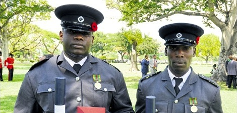 Correctional officers Ricardo Duncan (right) and Omar Robinson displaying their medals of honour for gallantry at the 2015 Ceremony of Investiture and Presentation of National Honours and Awards held at King's House yesterday.