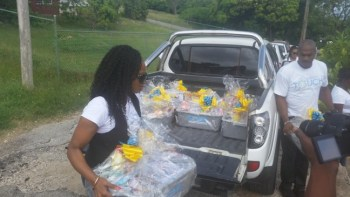 CEO Kaymar Jordan and IT Manager Henry Richards taking hampers to residents today.
