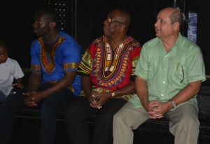 A member of the Israel Lovell drumming group is joined by MP Trevor Prescod (at centre) and Cuban Ambassador Francisco Pena in observing the libation.