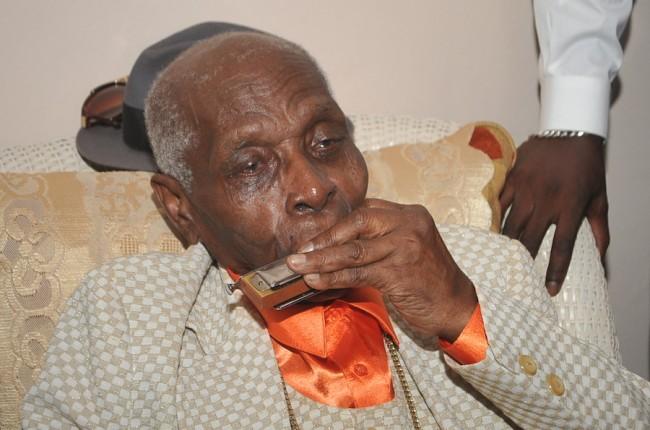 Centenarian Joseph Graham playing his harmonica.