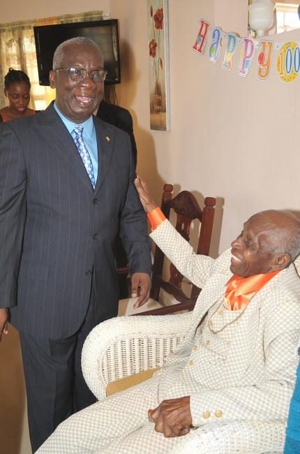 Minister of Education and Member of Parliament for Christ Church East Central Ronald Jones being greeted by centenarian Joseph Graham.