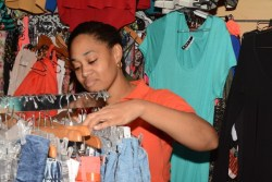 'Lady London' at the WOW boutique fixing clothing on a rack.