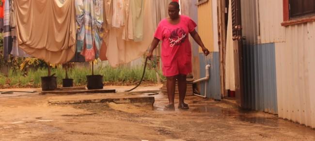 St Joseph resident Kim Headley hosing her backyard.