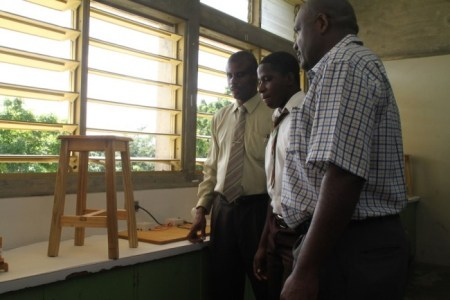 Shakeel Nicholls (at centre) showing off a stool he built to principal Jefferson Phillips (at left) and  teacher Kenmore Dalrymple.