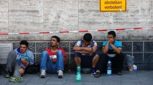 Migrants sitting outside the main station in Munich waiting to be registered.