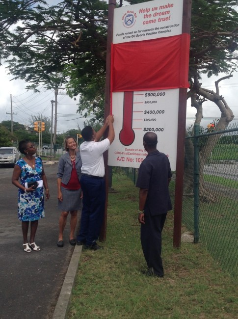 Student Johnathan Williams proudly unveiling the the Thermometer as project chairman Vivian-Anne Gittens, principal Dr David Browne and Give Back QC Charity trustee Professor M. Ann St John look on.