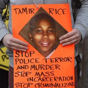 A protestor holding a sign with Tamir Rice's picture.