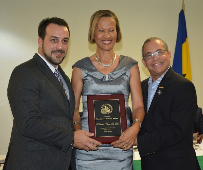 Awardee Dr Anne St John (at centre) with her plaque. At left is Rotary West president  Farid Mansoor and at right, Rotary district governor Milton Inniss.