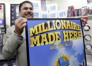 Balbir Atwal, the owner of a 7-Eleven store that sold a winning Powerball lottery ticket, holding up a Millionaire Made Here sign at his store in Chino Hills, California.