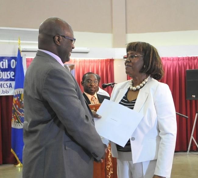 Reverend Dr Lucille Baird receiving her certificate from Attorney General Adriel Brathwaite.