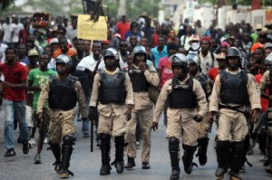 Haitian police patrol the street during a protest in Port-au-Prince yesterday.