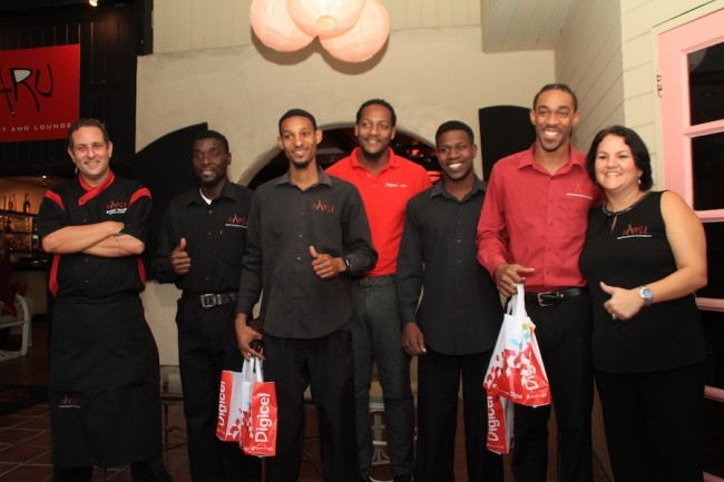 Digicel today presented new DL 1000 smartphones to Naru employees Nico Hutson, Kevin Payne, Joseph Grazette and Jabarry Worrell who selflessly rushed to the aid of two British visitors who were robbed on Monday. Here, they pose with Naru owners Lisa Evelyn-Taylor (right) and Barry Taylor (left), along with Digicel's Marketing Executive Marc Messiah (centre).