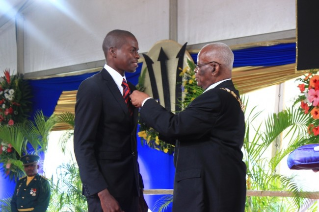Constable Jamal Ifill of the Royal Barbados Police Force receiving a Barbados Bravery Medal for the courage shown in saving the life of Margaret Walters who  had fallen into a septic tank.