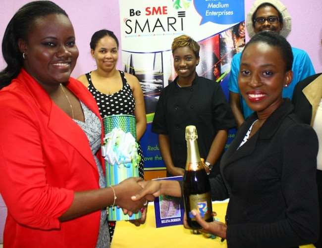 Kibibi Cumberbatch receiving her prize from Melissa Brathwaite of Miona Avenue, as Chief Executive Officer of the Small Business Association Lynette Holder and other participants look on.