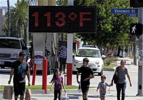 In this August 15, 2015 file photo, pedestrians walk past a digital thermometer reading 113 degrees Fahrenheit in the Canoga Park section of Los Angeles.