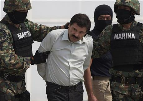 "In this February 22, 2014 file photo, Joaquin ""El Chapo"" Guzman being escorted to a helicopter in handcuffs by Mexican navy marines at a navy hanger in Mexico City, Mexico."