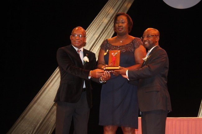 Mother of Jason Holder, Denise Holder, collects her son's award from NSC chairman  Michael Power and Minister of Sports Stephen Lashley (r).