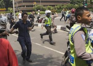 People, including unarmed police officers, fleeing from the scene after a gun battle broke out following an explosion in Jakarta, Indonesia, today.