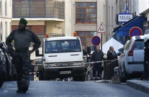 Police officers standing by the police station, seen in background right, after officers shot and killed a knife-wielding man wearing a fake explosives vest, in Paris, today.