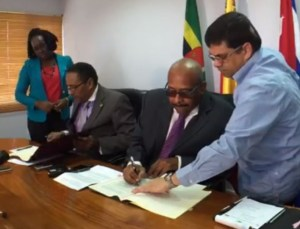 Minister of Health Dr Kenneth Darroux and (second right) and Ambassador Hayden Pirela Sanches (third right) signing the agreement today.