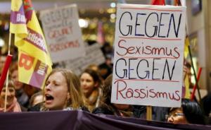 Women shouting slogans and holding up a placard that read Against Sexism –– Against Racism as they marched through the main railways station of Cologne, Germany, yesterday.